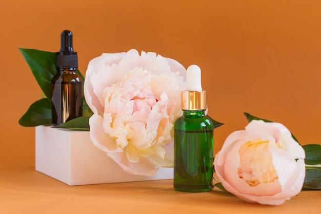 Dwie buteleczki z naturalnym ręcznie robionym serum i kwiatem piwonii na beżowym tle. samoopieka z organicznymi ręcznie robionymi kosmetykami.