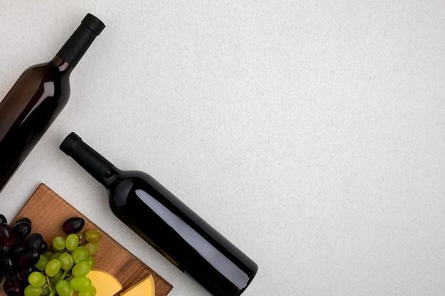 Dwie butelki białego i czerwonego wina sera i winogron widok z góry