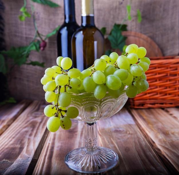 Dwie butelki czerwonego i białego wina na drewnianym stole z kiści winogron.selective focus.