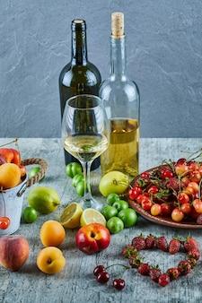 Dwie butelki i kieliszek wina na marmurowym stole z bukietem letnich świeżych owoców