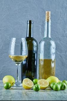 Dwie butelki i kieliszek wina na marmurowym stole z cytrynami i śliwkami wiśniowymi
