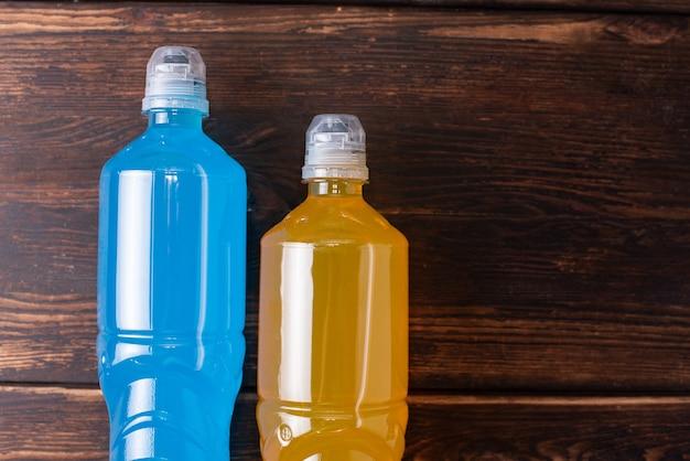 Dwie butelki koloru pomarańczowego i niebieskiego na ciemnym tle drewnianych, przywracając równowagę wody i soli po treningu sportowym, z bliska.