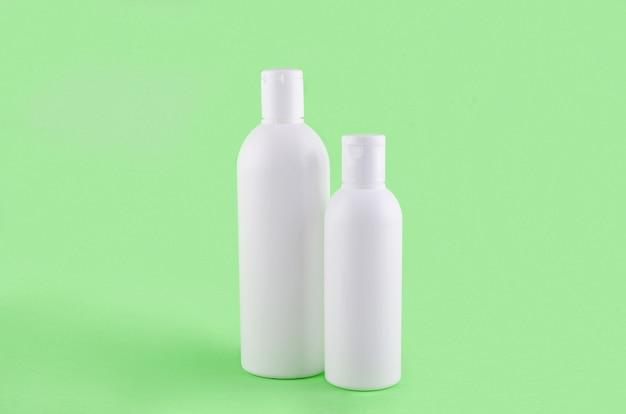Dwie butelki kosmetyczne na zielonym tle. zestaw produktów kosmetycznych do kremu, balsamu lub szamponu. koncepcja pielęgnacji włosów lub ciała. minimalna scena z pustym miejscem na podpis, makieta