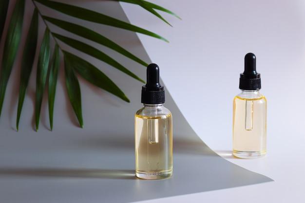 Dwie butelki kosmetycznego olejku eterycznego i liści palmowych serum do pielęgnacji skóry i przeciwstarzeniowy produkt kosmetyczny