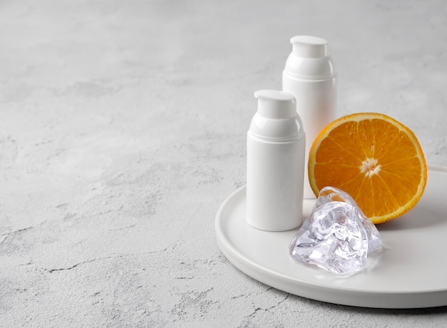 Dwie butelki kremu kosmetycznego z pomarańczą i lodem na szarym betonowym stole