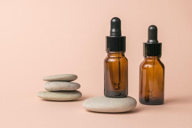 Dwie butelki na produkty medyczne i kamienie na beżowym tle.