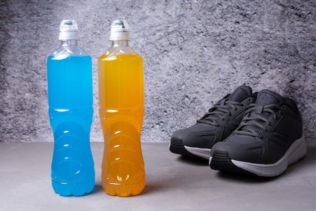 Dwie butelki napoju izotonicznego, przywracające równowagę wody i soli po treningu na szarym tle, zdrowy napój po aktywności sportowej, z bliska.