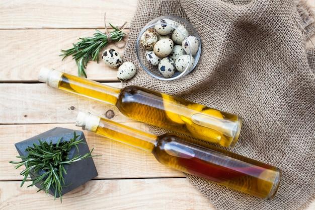 Dwie butelki oliwy z oliwek z pieprzem i cytryną leżące na lekkim drewnianym stole. dalej jest szklany dzbanek z jajkami przepiórczymi, garść świeżych kłamstw rozmarynu.