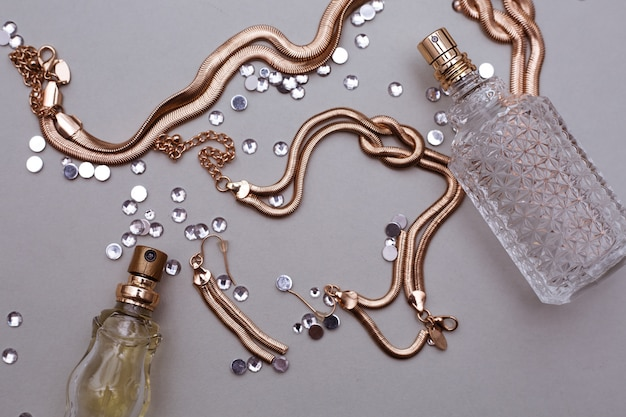 Dwie butelki perfum ze złotymi dodatkami jubilerskimi w szarym tle