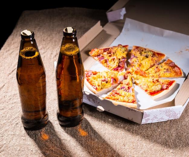 Dwie butelki piwa na stole pokrytym jutą obok pizzy rzemieślniczej podzielonej na plasterki ułożone w kartonowym pudełku na wynos