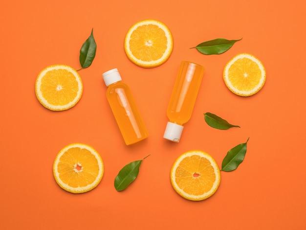 Dwie butelki soku pomarańczowego i pomarańczy z liśćmi na pomarańczowym tle. leżał płasko.