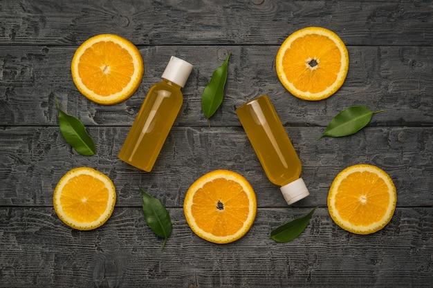 Dwie butelki soku pomarańczowego, liści i plastry pomarańczy na czarnym drewnianym stole.