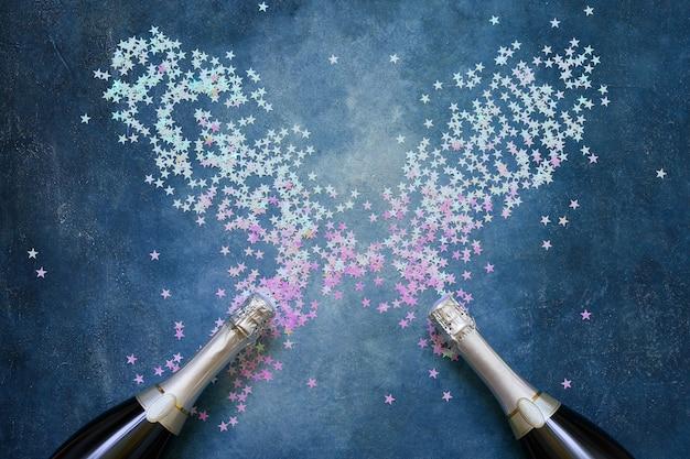 Dwie butelki szampana z holograficznymi gwiazdami konfetti na niebiesko. skopiuj miejsce, widok z góry