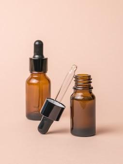 Dwie butelki wypełnione lekami na beżowym tle.