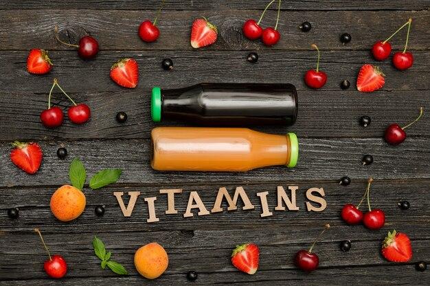 Dwie butelki z sokiem, owocami i napisem wegańskie na ciemnym drewnianym tle, koncepcja jedzenia