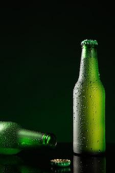 Dwie butelki zimnego piwa z kropli wody na ciemnozielonym tle z copyspace. format pionowy.