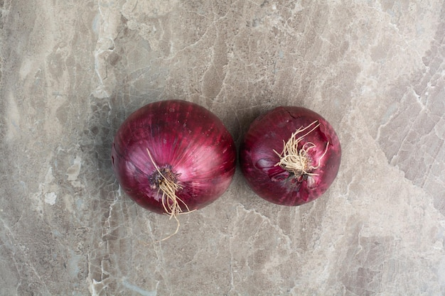 Dwie całe czerwone cebule cebulowe na marmurowym tle. zdjęcie wysokiej jakości