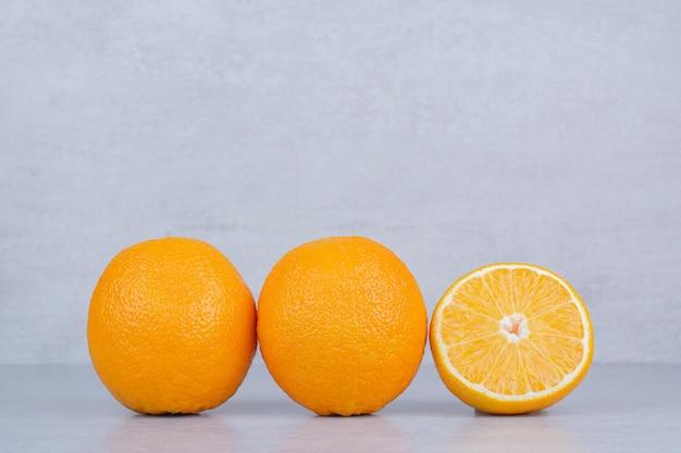 Dwie całe pomarańcze z plasterkiem na białym tle. zdjęcie wysokiej jakości