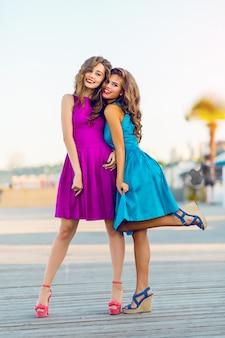 Dwie całkiem eleganckie kobiety w wieczorowych sukienkach koktajlowych spacerujące promenadą