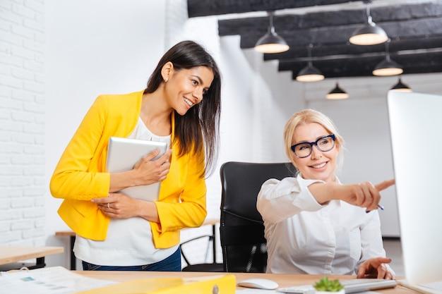 Dwie całkiem młode i dojrzałe kobiety w biurze po burzy mózgów przy stole w biurze