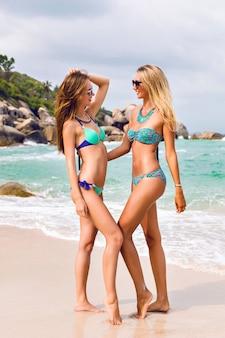Dwie całkiem najlepsze przyjaciółki bawią się na wakacjach, pozują na niesamowitej tropikalnej plaży z kamieniami i czystą błękitną wodą, ubrane w jasne stylowe bikini i okulary przeciwsłoneczne.