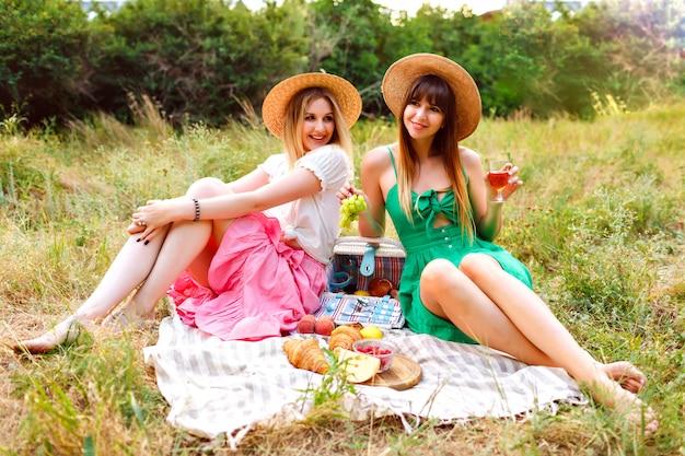 Dwie całkiem wesołe najlepsze przyjaciółki, ubrane w pasujące do siebie romantyczne eleganckie sukienki i słomkowe kapelusze