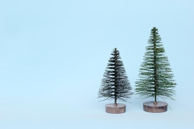 Dwie choinki na jasnym tle w minimalistycznym stylu. ozdoby świąteczne, koncepcja nowego roku i zimy.