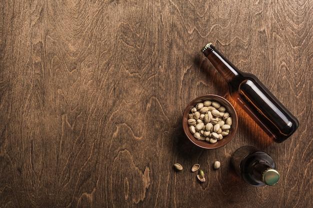 Dwie ciemne butelki piwa i talerz pistacji na drewnianym tle.