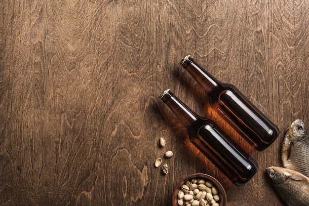 Dwie ciemne butelki piwa, suszone ryby i talerz pistacji na drewnianym tle.