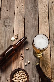 Dwie ciemne butelki piwa, szklanka piwa i piany oraz talerz pistacji na drewnianym tle.