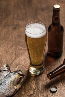 Dwie ciemne butelki piwa, szklanka piwa i piany, suszone ryby na drewnianym tle.