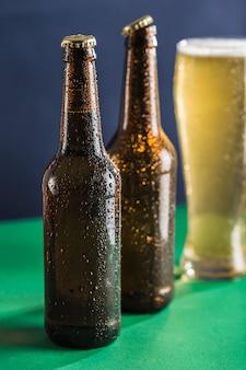 Dwie ciemne, zamglone butelki piwa i szklanka piwa i piany w tle na zielonym i niebieskim tle.