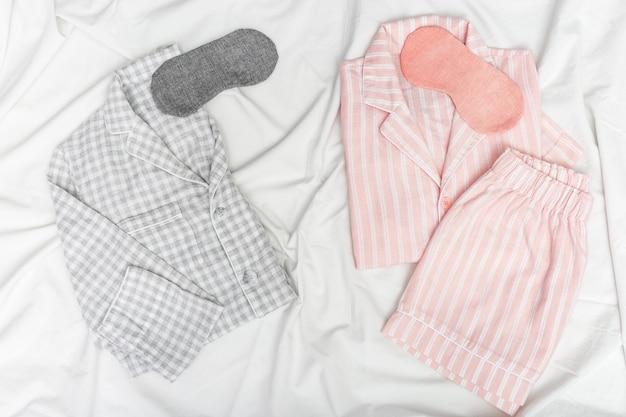 Dwie ciepłe piżamy na łóżku, męskie i żeńskie, maski na sen