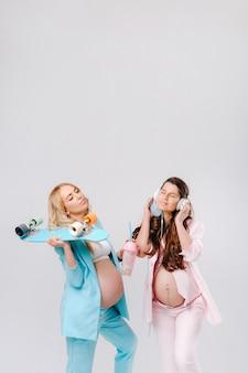 Dwie ciężarne dziewczyny w turkusowych i różowych garniturach ze szklankami soku, łyżwą i słuchawkami stoją na szarym tle