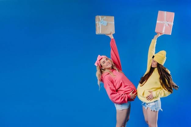 Dwie ciężarne dziewczyny z prezentami w rękach na niebieskim tle na białym tle