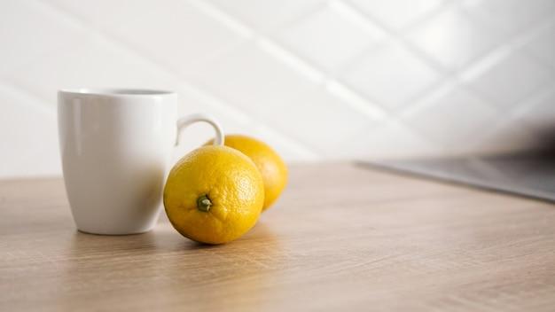 Dwie cytryny na kuchennym stole obok białego kubka herbaty. koncepcja rano