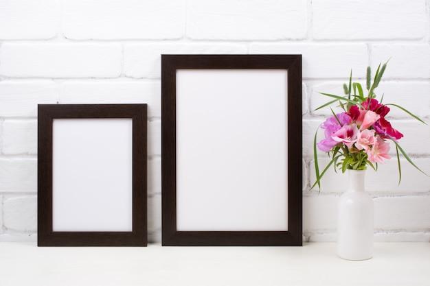 Dwie czarne brązowe ramki plakatowe z różowymi kwiatami clarkia
