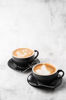 Dwie czarne filiżanki gorącej kawy latte z piękną mleczną pianką latte art texture na białym tle na jasnym tle marmuru. widok z góry, kopia przestrzeń. reklama menu kawiarni. menu kawiarni pionowy