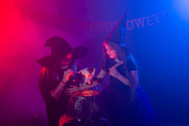 Dwie czarownice halloween czyniące magię z psem jack russell terrier w noc halloween. magia, święta i mistyczna koncepcja.