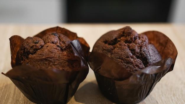 Dwie czekoladowe babeczki na drewnianym stole na tle nowoczesnej kuchni