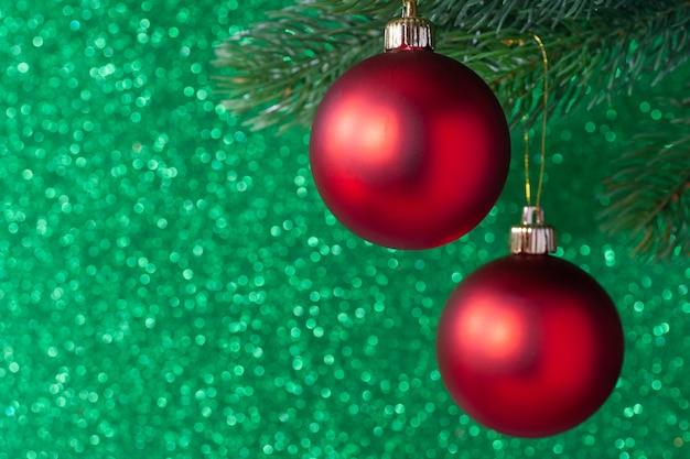 Dwie czerwone błyszczące piłki na gałęzi drzewa nowego roku na zielonym tle niewyraźne.