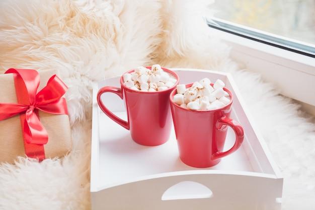 Dwie czerwone filiżanki gorącej czekolady z pianką na parapecie