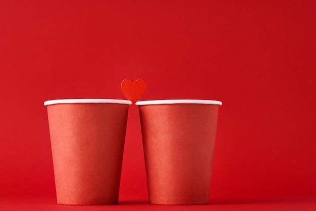 Dwie czerwone filiżanki kawy z sercem jak para zakochanych na czerwonej powierzchni. walentynki i romantyczna koncepcja