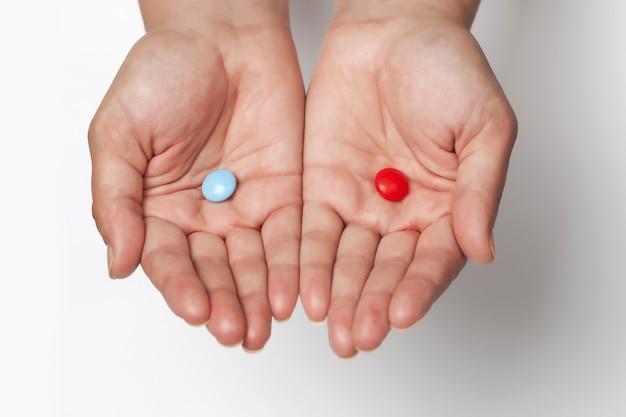 Dwie czerwone i niebieskie tabletki do wyboru na dłoniach z miejscem na tekst na białym tle