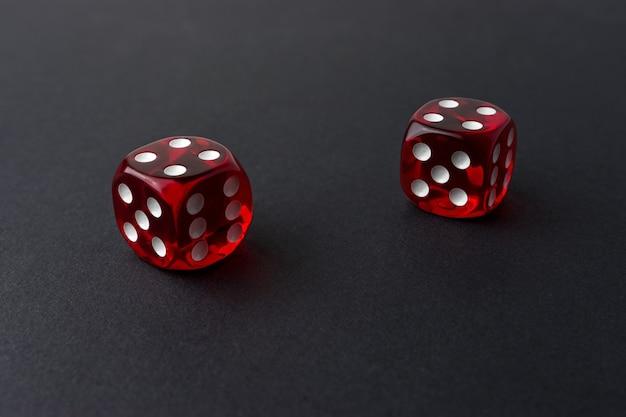 Dwie czerwone kostki do gry na czarnym stole