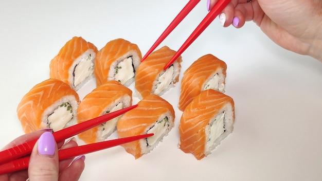 Dwie czerwone ręce pałeczkami biorąc sushi.