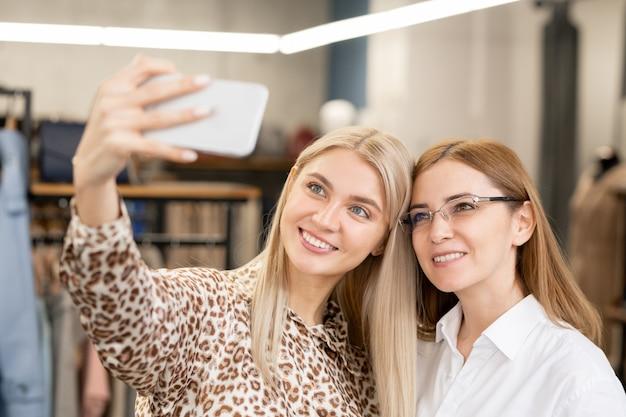 Dwie czule konsumenci uśmiechają się robiąc selfie przed aparatem w dziale odzieżowym podczas zakupów