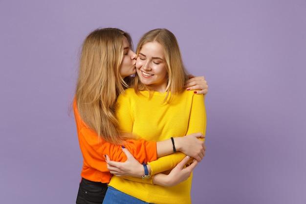 Dwie delikatne śliczne młode blondynki siostry bliźniaczki dziewczyny w żywe kolorowe ubrania przytulanie, całowanie w policzek na białym tle na pastelowej fioletowej niebieskiej ścianie. koncepcja życia rodzinnego osób. .