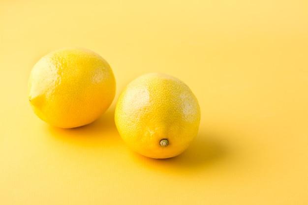Dwie dojrzałe całe cytryny na żółtym stole.