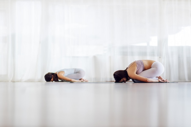 Dwie dopasowane joginki w pozycji jogi dziecka. wnętrze studia jogi.